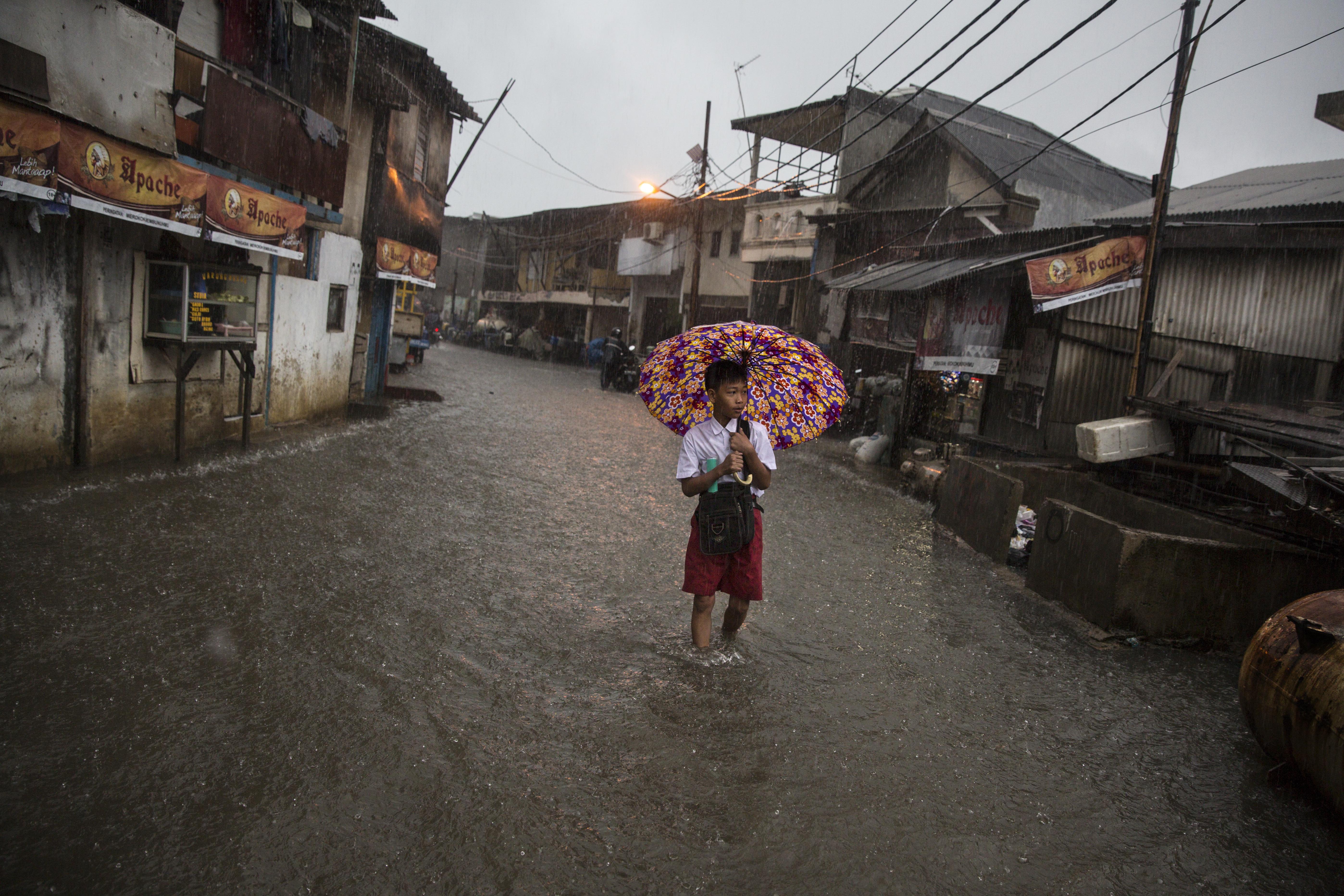 Na een dag van aanhoudende regens veranderen in de laaggelegen wijk Muara Baru de straten in rivieren.